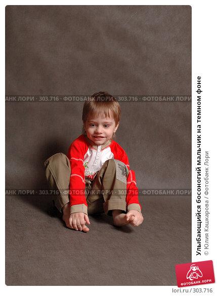 Улыбающийся босоногий мальчик на темном фоне, фото № 303716, снято 23 марта 2008 г. (c) Юлия Кашкарова / Фотобанк Лори
