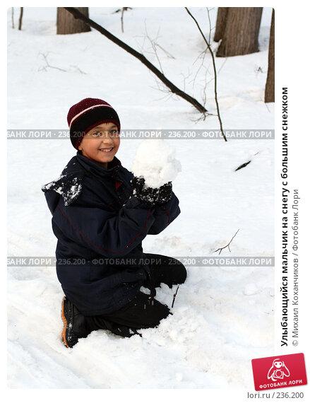 Купить «Улыбающийся мальчик на снегу с большим снежком», фото № 236200, снято 21 апреля 2018 г. (c) Михаил Коханчиков / Фотобанк Лори