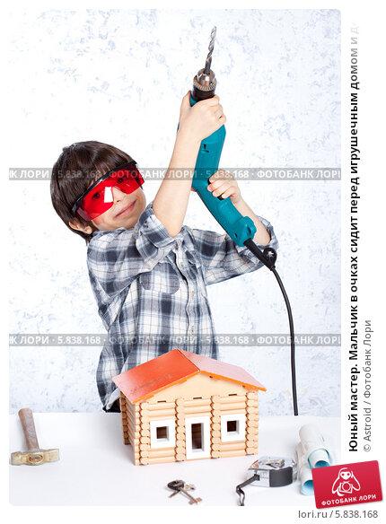 Купить «Юный мастер. Мальчик в очках сидит перед игрушечным домом и держит в руках дрель», фото № 5838168, снято 28 марта 2014 г. (c) Astroid / Фотобанк Лори