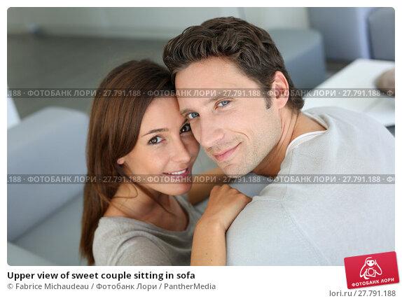 Купить «Upper view of sweet couple sitting in sofa», фото № 27791188, снято 18 февраля 2018 г. (c) PantherMedia / Фотобанк Лори