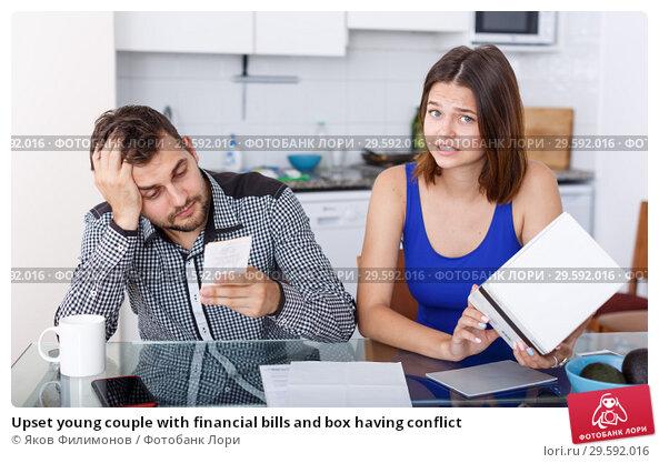 Купить «Upset young couple with financial bills and box having conflict», фото № 29592016, снято 6 июля 2018 г. (c) Яков Филимонов / Фотобанк Лори