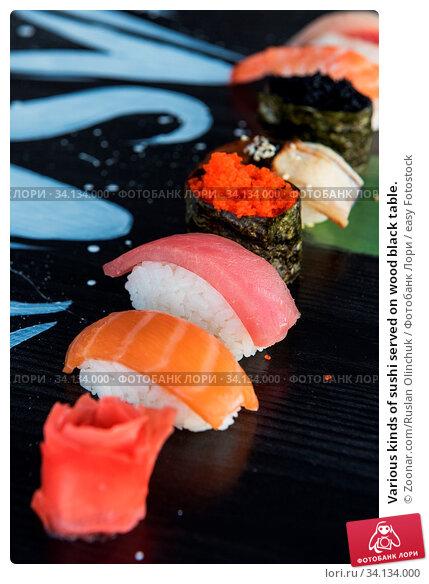 Купить «Various kinds of sushi served on wood black table.», фото № 34134000, снято 6 июля 2020 г. (c) easy Fotostock / Фотобанк Лори