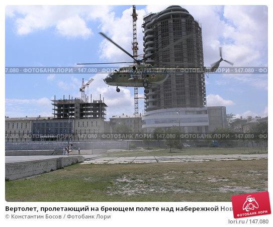 Вертолет, пролетающий на бреющем полете над набережной Новороссийска на фоне строящегося дома, фото № 147080, снято 1 июля 2005 г. (c) Константин Босов / Фотобанк Лори