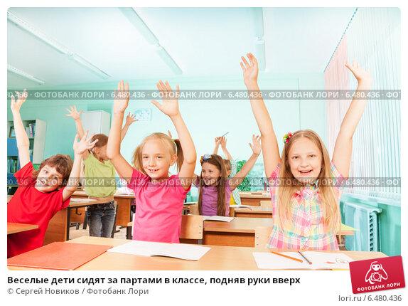 Купить «Веселые дети сидят за партами в классе, подняв руки вверх», фото № 6480436, снято 16 августа 2014 г. (c) Сергей Новиков / Фотобанк Лори