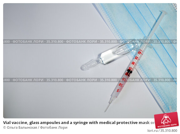 Vial vaccine, glass ampoules and a syringe with medical protective mask on white background, global vaccination concept. Стоковое фото, фотограф Ольга Балынская / Фотобанк Лори