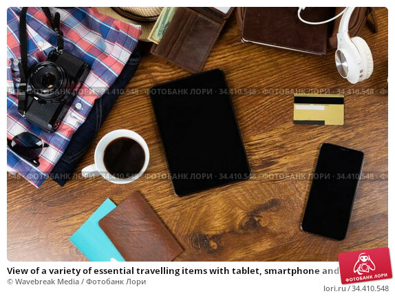 View of a variety of essential travelling items with tablet, smartphone and camera on wooden table. Стоковое фото, агентство Wavebreak Media / Фотобанк Лори