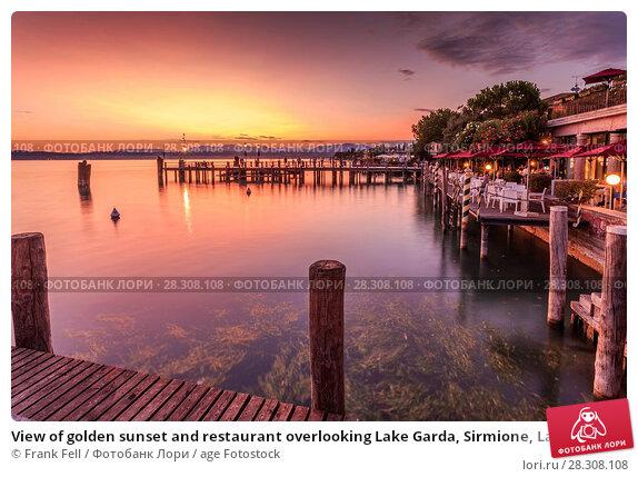 Купить «View of golden sunset and restaurant overlooking Lake Garda, Sirmione, Lake Garda, Lombardy, Italian Lakes, Italy, Europe», фото № 28308108, снято 21 августа 2017 г. (c) age Fotostock / Фотобанк Лори