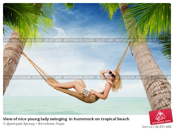 Купить «View of nice young lady swinging  in hummock on tropical beach», фото № 26551440, снято 23 ноября 2017 г. (c) Дмитрий Эрслер / Фотобанк Лори