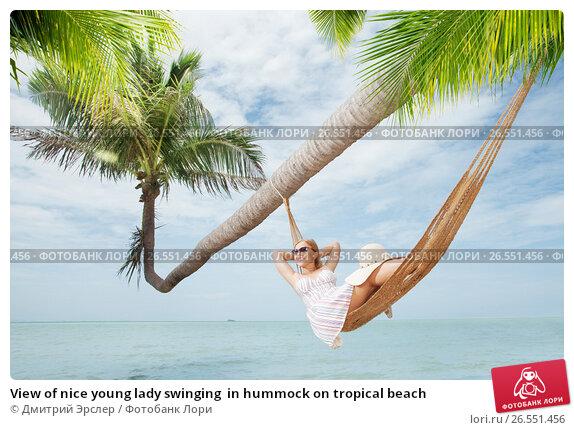 View of nice young lady swinging  in hummock on tropical beach, фото № 26551456, снято 24 августа 2017 г. (c) Дмитрий Эрслер / Фотобанк Лори