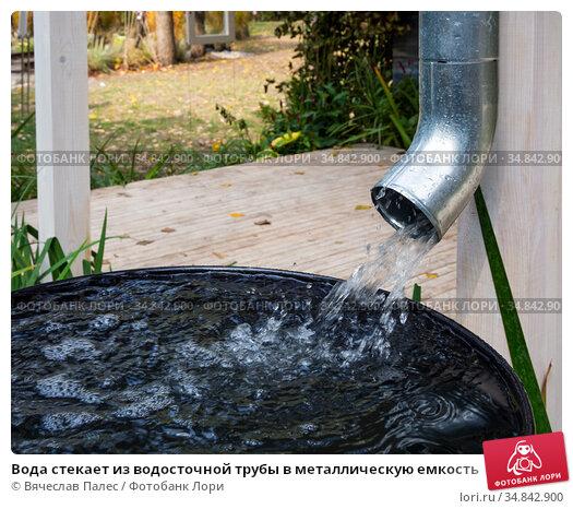 Вода стекает из водосточной трубы в металлическую емкость. Стоковое фото, фотограф Вячеслав Палес / Фотобанк Лори
