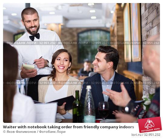 Waiter with notebook taking order from friendly company indoors. Стоковое фото, фотограф Яков Филимонов / Фотобанк Лори