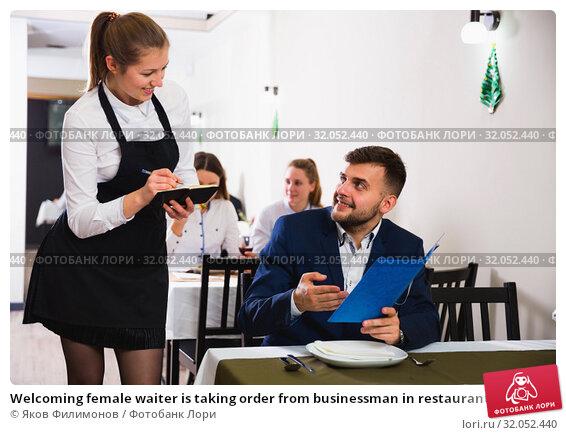 Welcoming female waiter is taking order from businessman in restaurante. Стоковое фото, фотограф Яков Филимонов / Фотобанк Лори