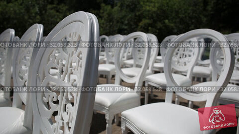 White chairs and Wedding decorations from white and red flowers ceremony floristics near the sea. Стоковое видео, видеограф Aleksejs Bergmanis / Фотобанк Лори