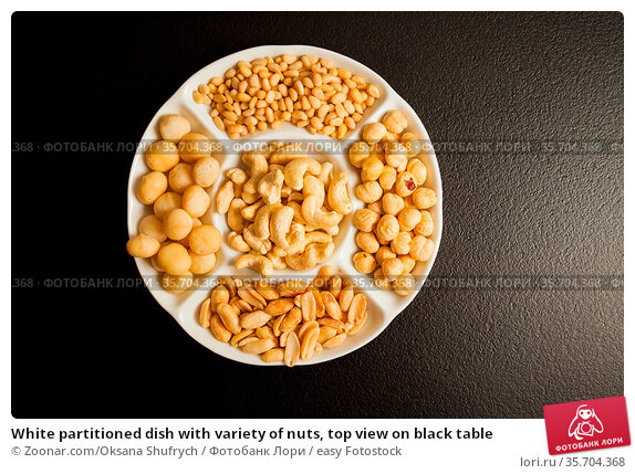 White partitioned dish with variety of nuts, top view on black table. Стоковое фото, фотограф Zoonar.com/Oksana Shufrych / easy Fotostock / Фотобанк Лори