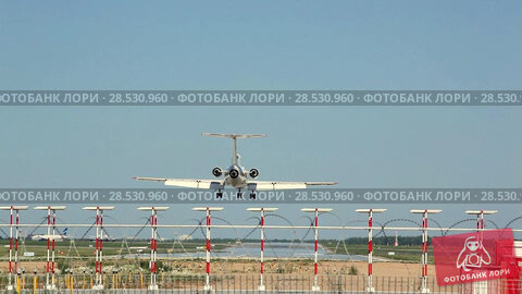 Купить «White plane lands on the runway on the background of airport», видеоролик № 28530960, снято 4 июня 2018 г. (c) Mikhail Starodubov / Фотобанк Лори