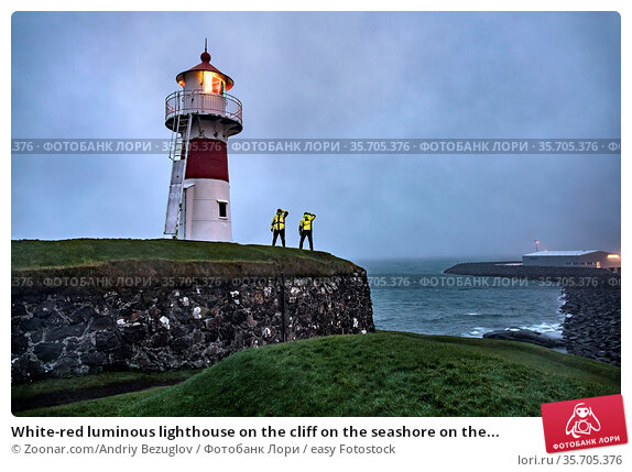 White-red luminous lighthouse on the cliff on the seashore on the... Стоковое фото, фотограф Zoonar.com/Andriy Bezuglov / easy Fotostock / Фотобанк Лори