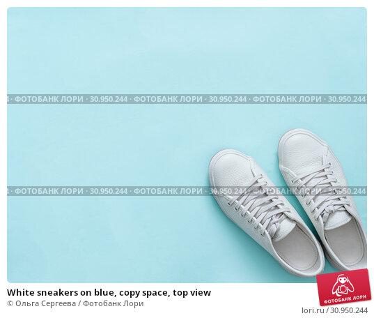 Купить «White sneakers on blue, copy space, top view», фото № 30950244, снято 9 мая 2019 г. (c) Ольга Сергеева / Фотобанк Лори