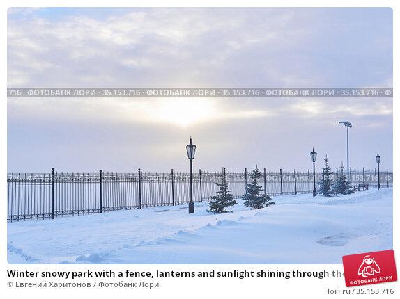 Winter snowy park with a fence, lanterns and sunlight shining through the clouds. Стоковое фото, фотограф Евгений Харитонов / Фотобанк Лори