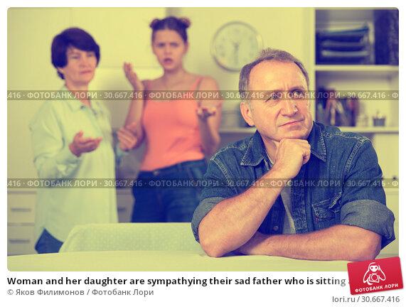 Купить «Woman and her daughter are sympathying their sad father who is sitting at the table», фото № 30667416, снято 25 октября 2017 г. (c) Яков Филимонов / Фотобанк Лори