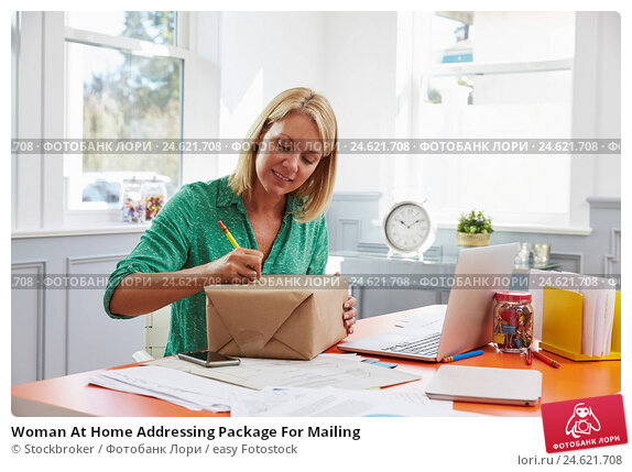 Купить «Woman At Home Addressing Package For Mailing», фото № 24621708, снято 13 октября 2015 г. (c) easy Fotostock / Фотобанк Лори