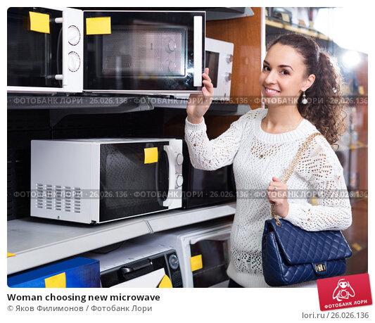 Купить «Woman choosing new microwave», фото № 26026136, снято 22 марта 2019 г. (c) Яков Филимонов / Фотобанк Лори