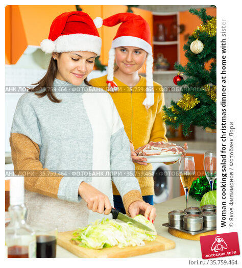 Woman cooking salad for christmas dinner at home with sister. Стоковое фото, фотограф Яков Филимонов / Фотобанк Лори