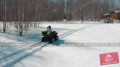 Купить «Woman driving on ATV along the forest on the snow track», видеоролик № 30925360, снято 25 июня 2019 г. (c) Константин Шишкин / Фотобанк Лори