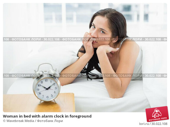 Купить «Woman in bed with alarm clock in foreground», фото № 30022108, снято 10 июля 2013 г. (c) Wavebreak Media / Фотобанк Лори