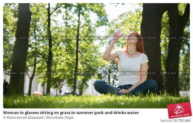 Woman in glasses sitting on grass in summer park and drinks water, фото № 26755084, снято 3 июля 2017 г. (c) Константин Шишкин / Фотобанк Лори