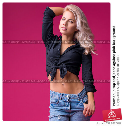 Woman in top and jeans against pink background. Стоковое фото, фотограф Гурьянов Андрей / Фотобанк Лори