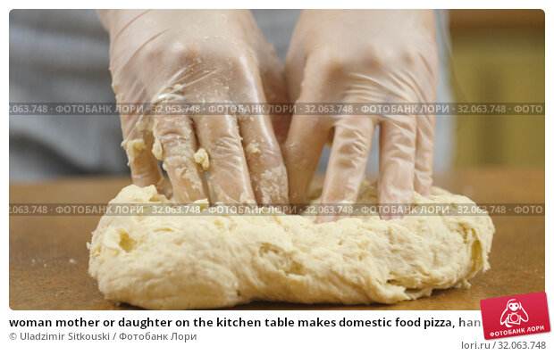 woman mother or daughter on the kitchen table makes domestic food pizza, hands work and pushing stir knead the dough, selective focus dolly shot. Стоковое фото, фотограф Uladzimir Sitkouski / Фотобанк Лори