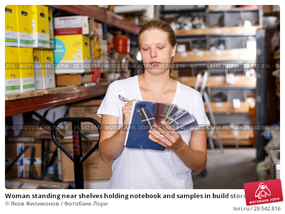Купить «Woman standing near shelves holding notebook and samples in build store», фото № 29542816, снято 20 сентября 2018 г. (c) Яков Филимонов / Фотобанк Лори