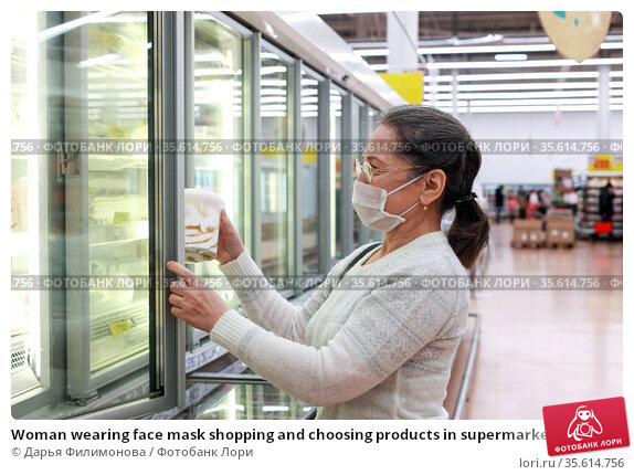 Woman wearing face mask shopping and choosing products in supermarket. Стоковое фото, фотограф Дарья Филимонова / Фотобанк Лори