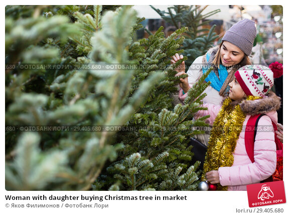Купить «Woman with daughter buying Christmas tree in market», фото № 29405680, снято 23 февраля 2019 г. (c) Яков Филимонов / Фотобанк Лори