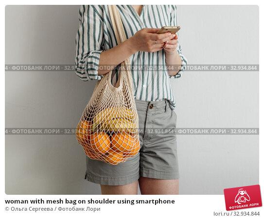 Купить «woman with mesh bag on shoulder using smartphone», фото № 32934844, снято 1 июля 2019 г. (c) Ольга Сергеева / Фотобанк Лори