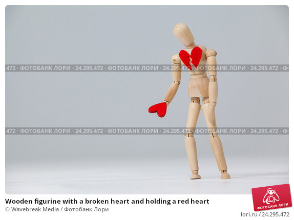 Купить «Wooden figurine with a broken heart and holding a red heart», фото № 24295472, снято 23 августа 2016 г. (c) Wavebreak Media / Фотобанк Лори