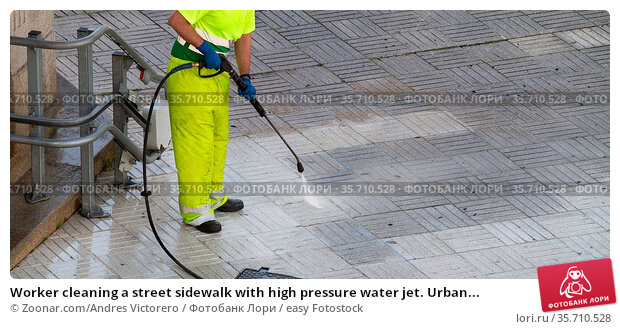 Worker cleaning a street sidewalk with high pressure water jet. Urban... Стоковое фото, фотограф Zoonar.com/Andres Victorero / easy Fotostock / Фотобанк Лори