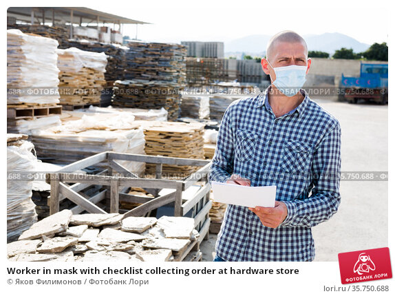 Worker in mask with checklist collecting order at hardware store. Стоковое фото, фотограф Яков Филимонов / Фотобанк Лори