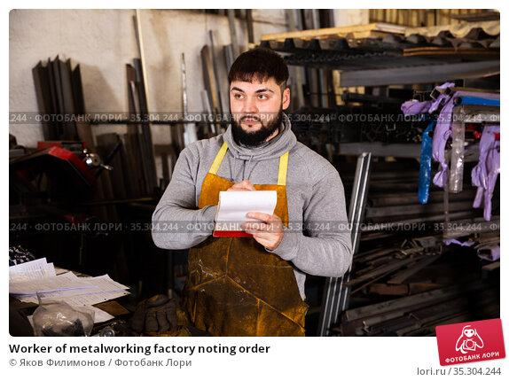 Worker of metalworking factory noting order. Стоковое фото, фотограф Яков Филимонов / Фотобанк Лори