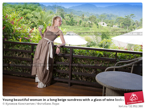 Young beautiful woman in a long beige sundress with a glass of wine looks over his shoulder from the terrace to the tropical nature. Стоковое фото, фотограф Куликов Константин / Фотобанк Лори