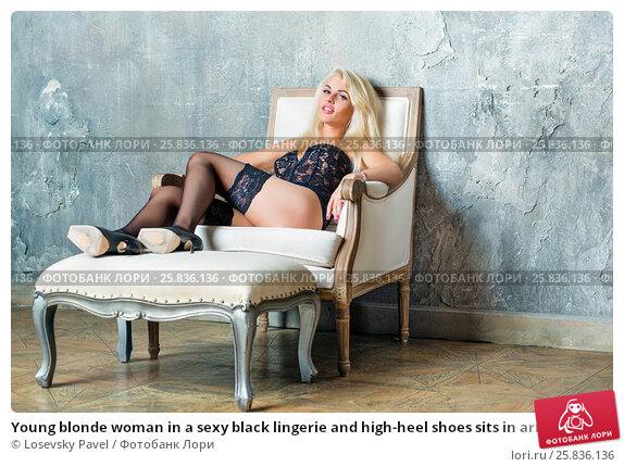 Купить «Young blonde woman in a sexy black lingerie and high-heel shoes sits in armchair with her feet on footrest in empty room», фото № 25836136, снято 17 сентября 2015 г. (c) Losevsky Pavel / Фотобанк Лори