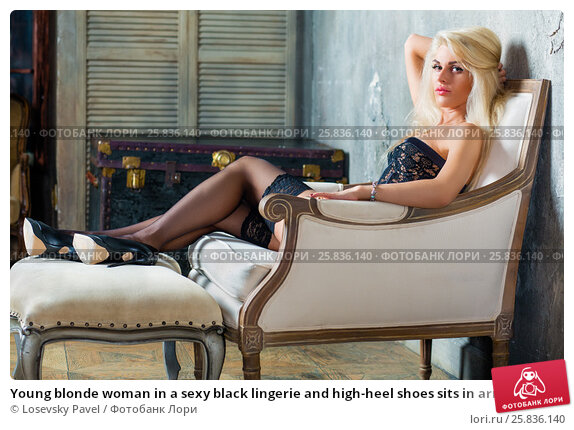 Купить «Young blonde woman in a sexy black lingerie and high-heel shoes sits in armchair with one hand under head and her feet on footrest», фото № 25836140, снято 17 сентября 2015 г. (c) Losevsky Pavel / Фотобанк Лори