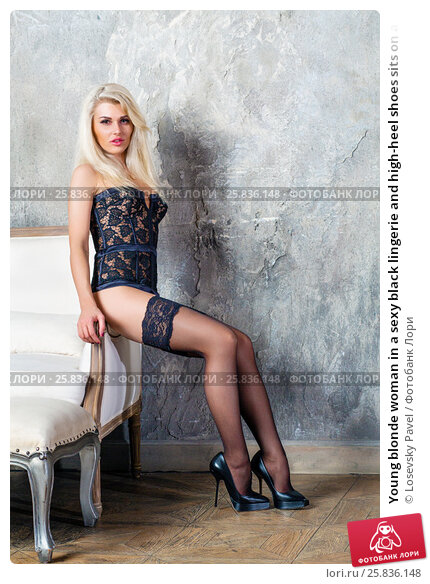 Купить «Young blonde woman in a sexy black lingerie and high-heel shoes sits on armrest of armchair in room», фото № 25836148, снято 17 сентября 2015 г. (c) Losevsky Pavel / Фотобанк Лори