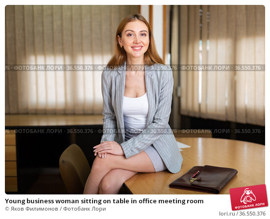 Young business woman sitting on table in office meeting room. Стоковое фото, фотограф Яков Филимонов / Фотобанк Лори