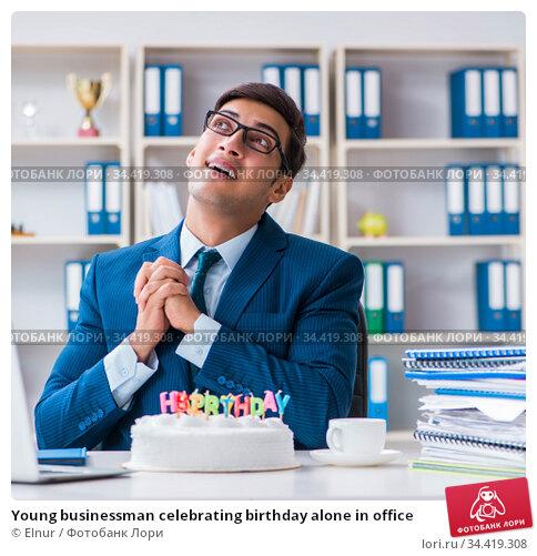 Young businessman celebrating birthday alone in office. Стоковое фото, фотограф Elnur / Фотобанк Лори