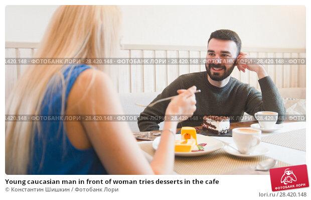 Купить «Young caucasian man in front of woman tries desserts in the cafe», фото № 28420148, снято 27 мая 2018 г. (c) Константин Шишкин / Фотобанк Лори