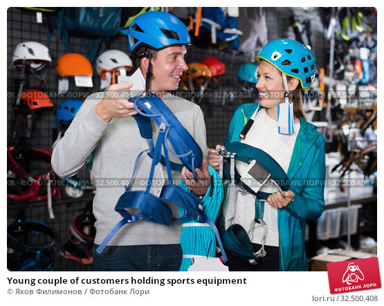Купить «Young couple of customers holding sports equipment», фото № 32500408, снято 25 октября 2017 г. (c) Яков Филимонов / Фотобанк Лори