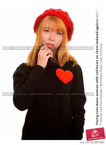 Young cute Asian woman with red heart on chest isolated against white background. Стоковое фото, фотограф Zoonar.com/Toni Rantala / easy Fotostock / Фотобанк Лори
