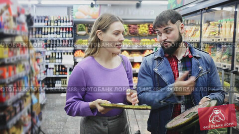 Young family couple standing near refrigeration showcase in supermarket, choosing frozen pizza. Стоковое видео, видеограф Яков Филимонов / Фотобанк Лори