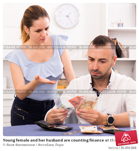 Young female and her husband are counting finance at the table. Стоковое фото, фотограф Яков Филимонов / Фотобанк Лори